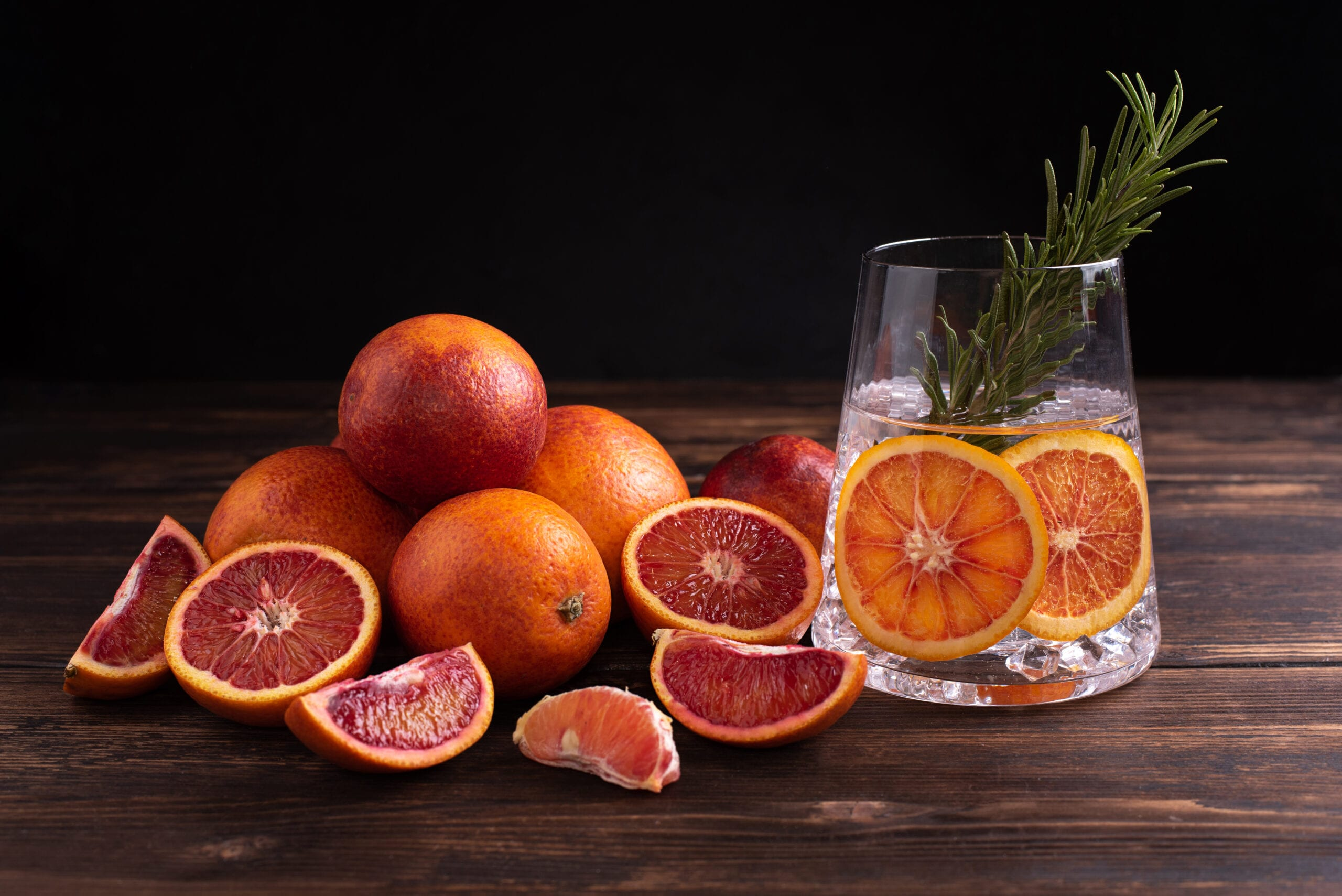 Blood Orange and Rosemary Gin presented in a glass tumbler. Blood orange fruits have been laid out on the table.