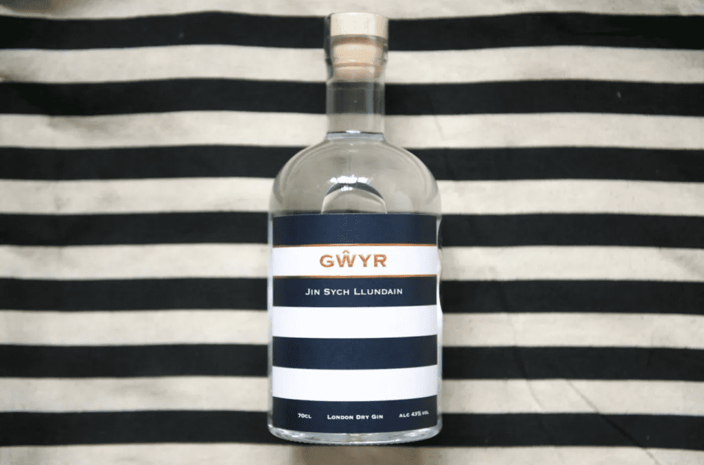 A bottle of gin on a blue and white stripe background