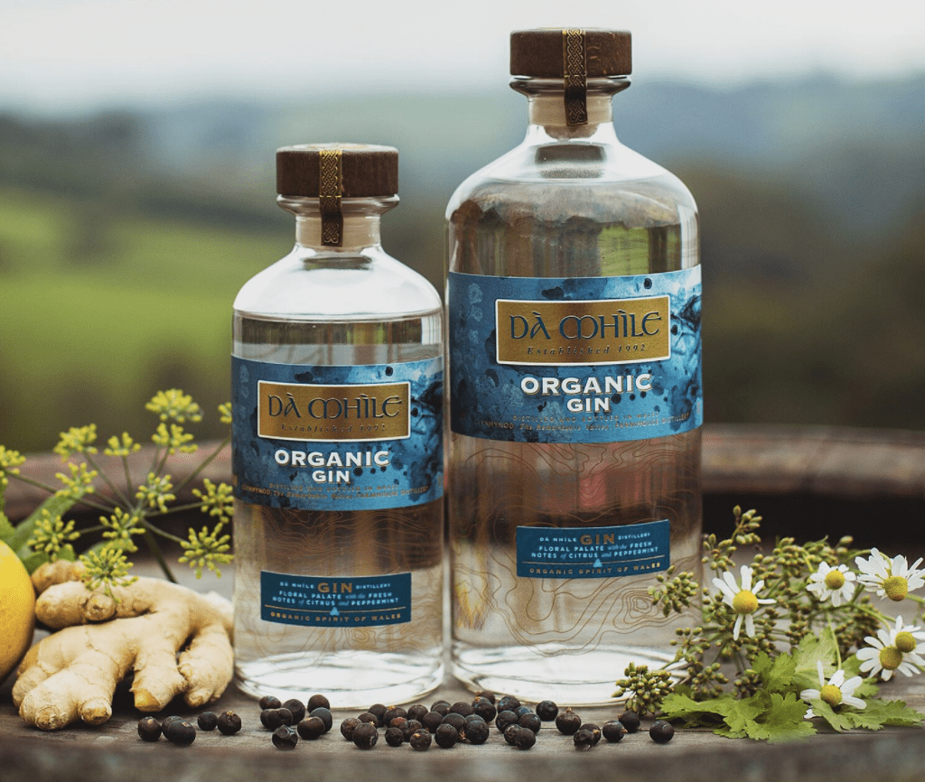 Two bottles of organic gin against a landscaoe of green rolling hills.